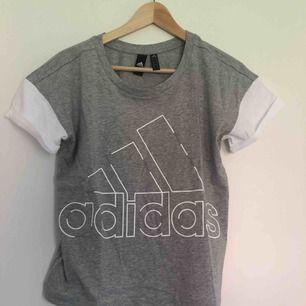 Grå och vit adidas T-shirt, perfekt till vardag men även träning! Frakt tillkommer