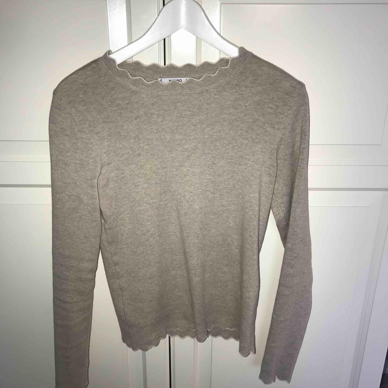 En beige tröja från Mango med vita volangsömmar längst kanterna. Storlek S, använd endast en gång så säljer pga att den tyvärr aldrig kommer till användning. 120kr exkl frakt. Toppar.