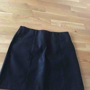 Kjol i svart imitationsläder från NLY. Aldrig använd och frakt ingår ej!