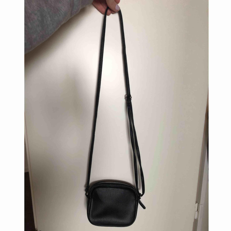 Smidig liten svart väska i fuskskinn från h&m.  Justerbart axelband. Mötas upp i sthlm eller skickar på posten, köparen betalar frakt.. Väskor.