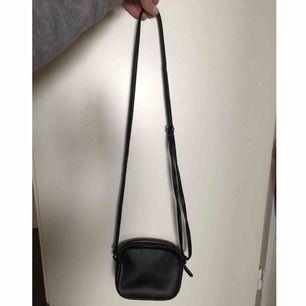 Smidig liten svart väska i fuskskinn från h&m.  Justerbart axelband. Mötas upp i sthlm eller skickar på posten, köparen betalar frakt.