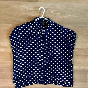 Blus/skjorta marinblå med vita hjärtan. 7 knappar framtill. Fint fall. Från topshop. Litet hål i sömmen vid nedersta knappen men kan lagas enkelt! Jag kan laga om så önskas :)