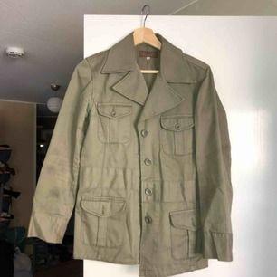 En militärgrön jacka köpt secondhand.