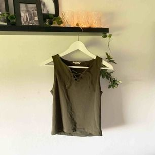 Militärgrönt linne med snörningsdetalj i fram. Toppen av snörena är slitna.