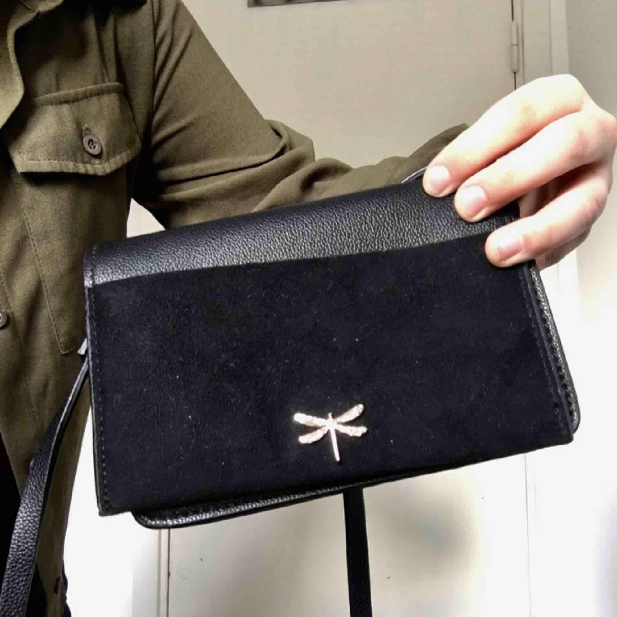 Liten svart handväska med gulddetalj från H&M.. Väskor.
