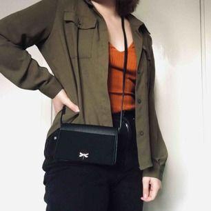 Liten svart handväska med gulddetalj från H&M.