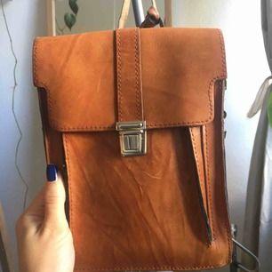 Jättefin brun axelremsväska i läder. Inköpt på loppis och i toppenskick. Finns litet ytterfack för ex. busskort och ryms mobil plånbok och lite till i själva väskan.