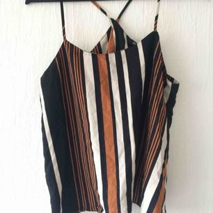 Fint oanvänt linne med korsade band och öppen rygg.