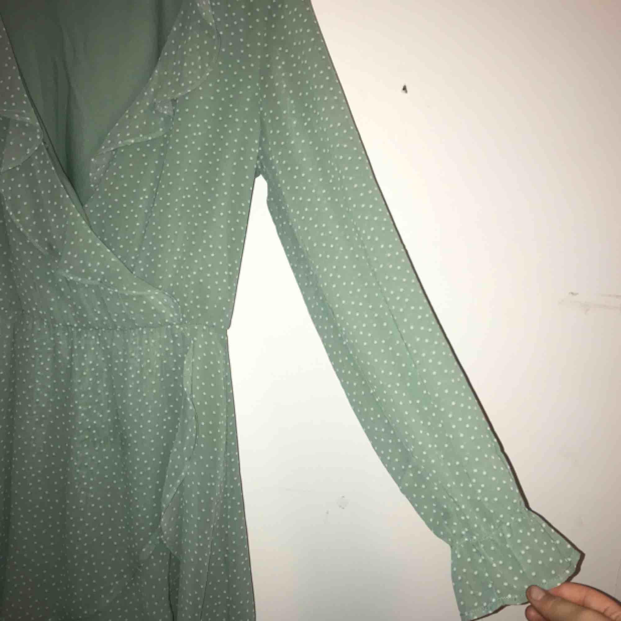 Poka dotted klänning med volanger i en mintgrön färg. Klänningar.