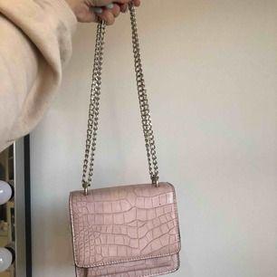 Super söt liten väska från Nelly. Kan bäras på två sätt! Väskan är i ljusrosa skinn imitation.