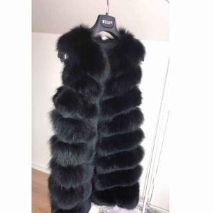 En väldigt fin svart pälsväst med äkta päls. Använd endast vid 1 tillfälle då jag har flera antal pälsvästar. Väldigt fin och varm. Denna är den långa modellen som är 90 cm  Nypris;- 6000kr!