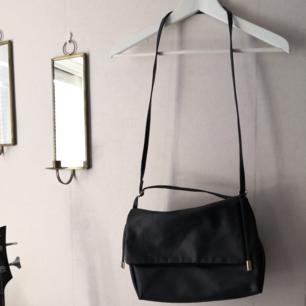 Så snygg väska som går att använda med lång och kort rem! Svart läderimitation med guld detaljer