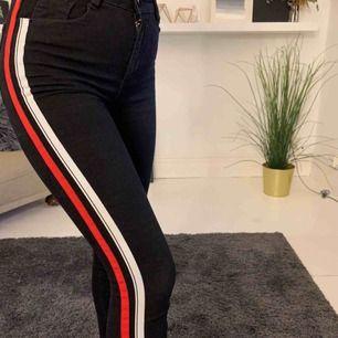 Svarta stretchiga jeans med röd och vit rand längs sidan  Orsak: använder inte :/