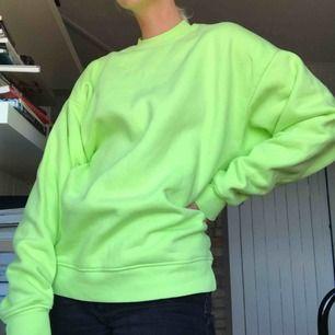 Neongrön sweatshirt från Weekday. Aldrig använd. Boxig modell med tajt hals. Köparen står för frakt eller möts i Gbg✨