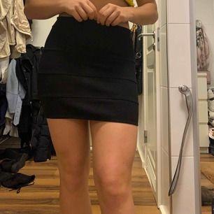 Kort, svart kjol från H&M med silvrig dragkedja baktill.