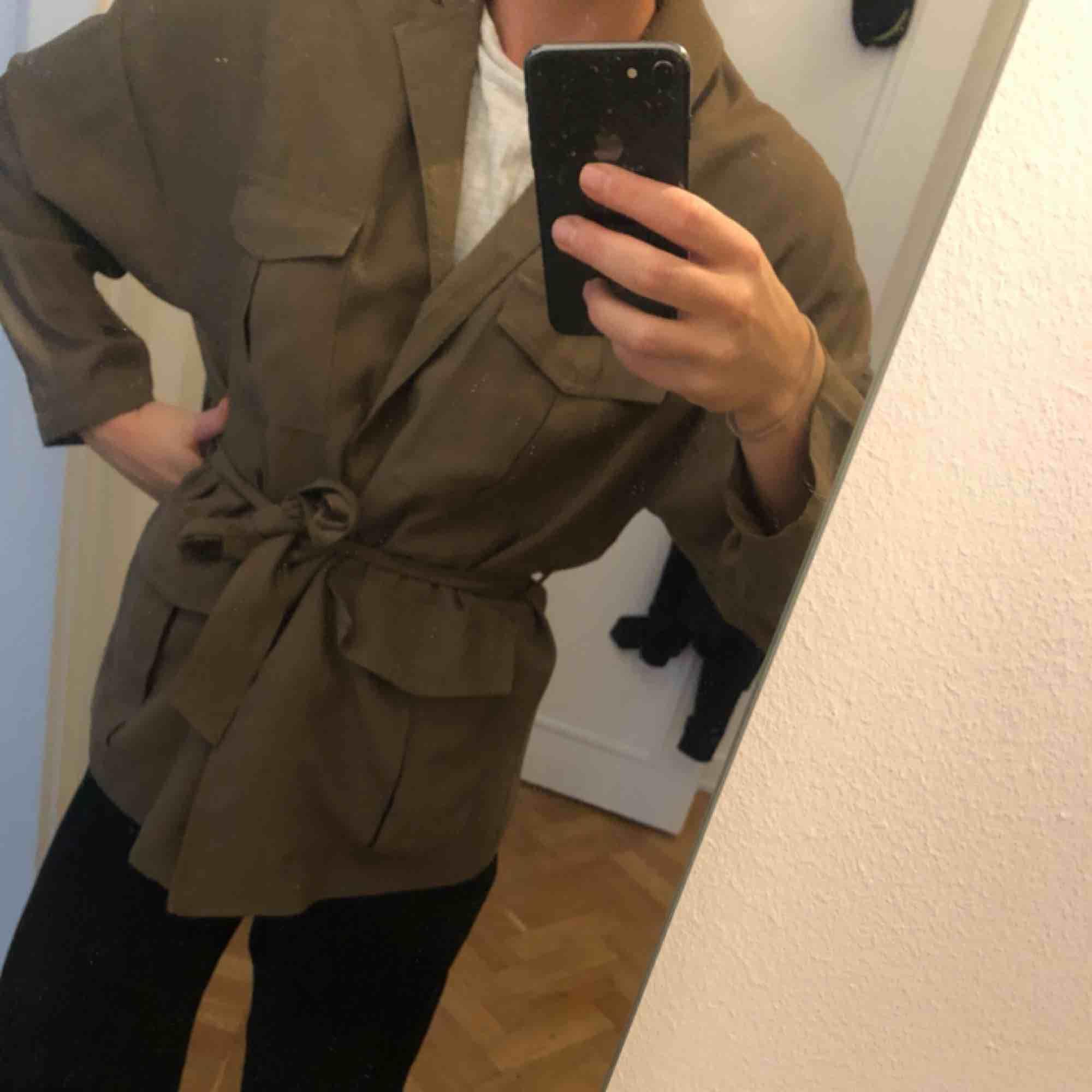 Carin Wester jacka olivgrön/militärgrön  Knäppning och midjeband. Snygg även utan midjebandet.   Säljer av min garderob på sådant jag inte använder. Denna jacka är väldigt sparsamt använd: ca 5 ggr  . Jackor.