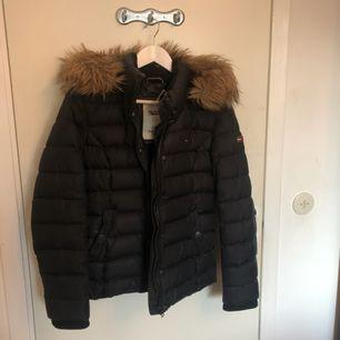 Säljer en svart Tommy Hilfiger jacka med avtagbara luva och päls. Jackan är köpt på Bubbleroom för  2199kr