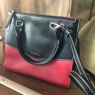 Väldigt fin och cool röd och svart handväska från fiorelli  Kör för ca 400-500kr  Kan mötas i nacka eller i slussen! Om köparen vill ha väskan skickad till sig står köparen för frakten  Betalning sker via swish