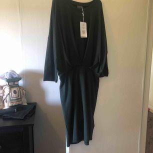 Mörkgrön klänning med tight kjol och mer löst sittande överdel. Endast testad och tvättad. Kan skickas om köparen står för frakten.