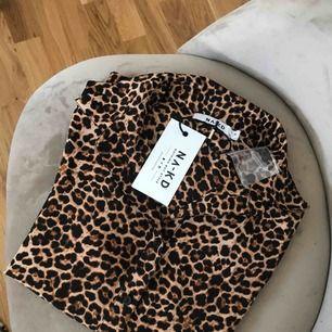 En helt ny leopard skjorta med knyt på ärmarna med lappar kvar. Köparen står för frakten.
