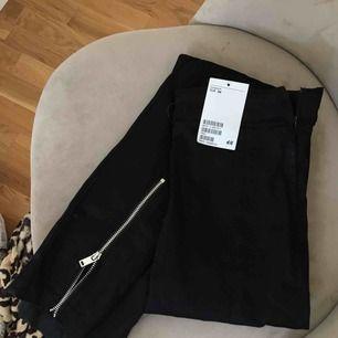 Helt ny svart byxa med dragkedja framtill på benslutet med lappar kvar. Köparen står för frakten.