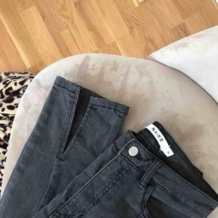 Ett par gråa jeans med slits från Nakd. Köparen står för frakten.