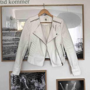 En vit skinnjacka med silvriga detaljer. Köparen står för frakten.