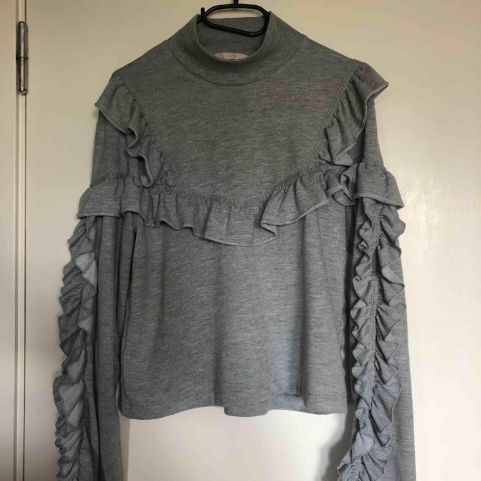 Charmig grå tröja med volanger från H&M. Använd 1-2 ggr. Kan mötas upp i Västerås eller frakta (fraktkostnad tillkommer). Fler bilder kan skickas på plagget vid intresse!. Tröjor & Koftor.