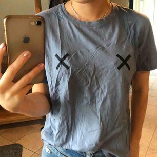 Super snygg gråblå t-shirt med kors på brösten. Säljer pågrund av att jag inte använder det längre, men är i bra skick.