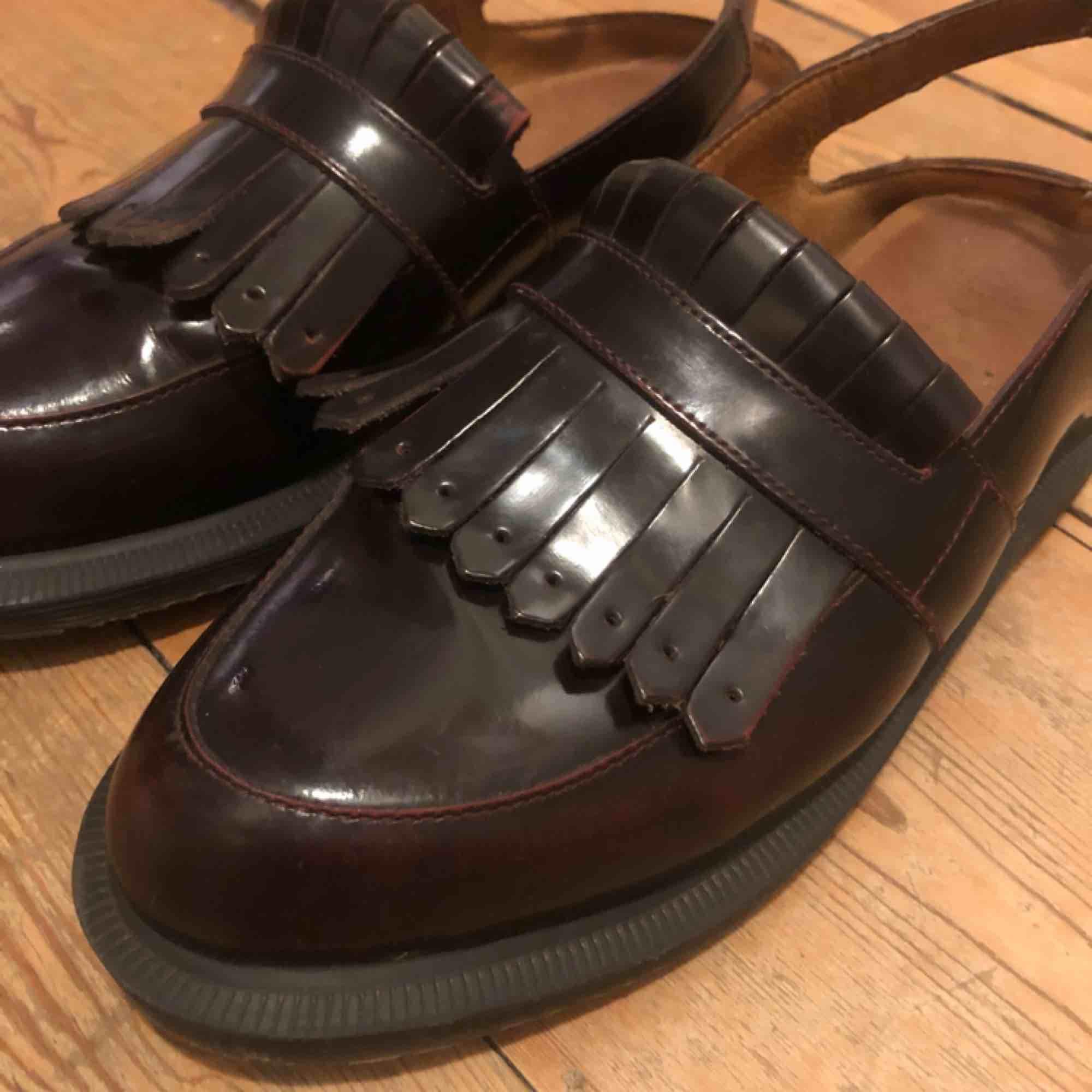 """Säljer ett par underbara halvöppna loafers i mörkt vinrött från Dr Martens. Storlek 39 med normal passform. Väldigt sköna med rejäl sula, resårinlägg vid hälen och klippta """"fransar"""" i läder. Mycket sparsamt använda och i toppskick. Nypris ca 1500kr. . Skor."""