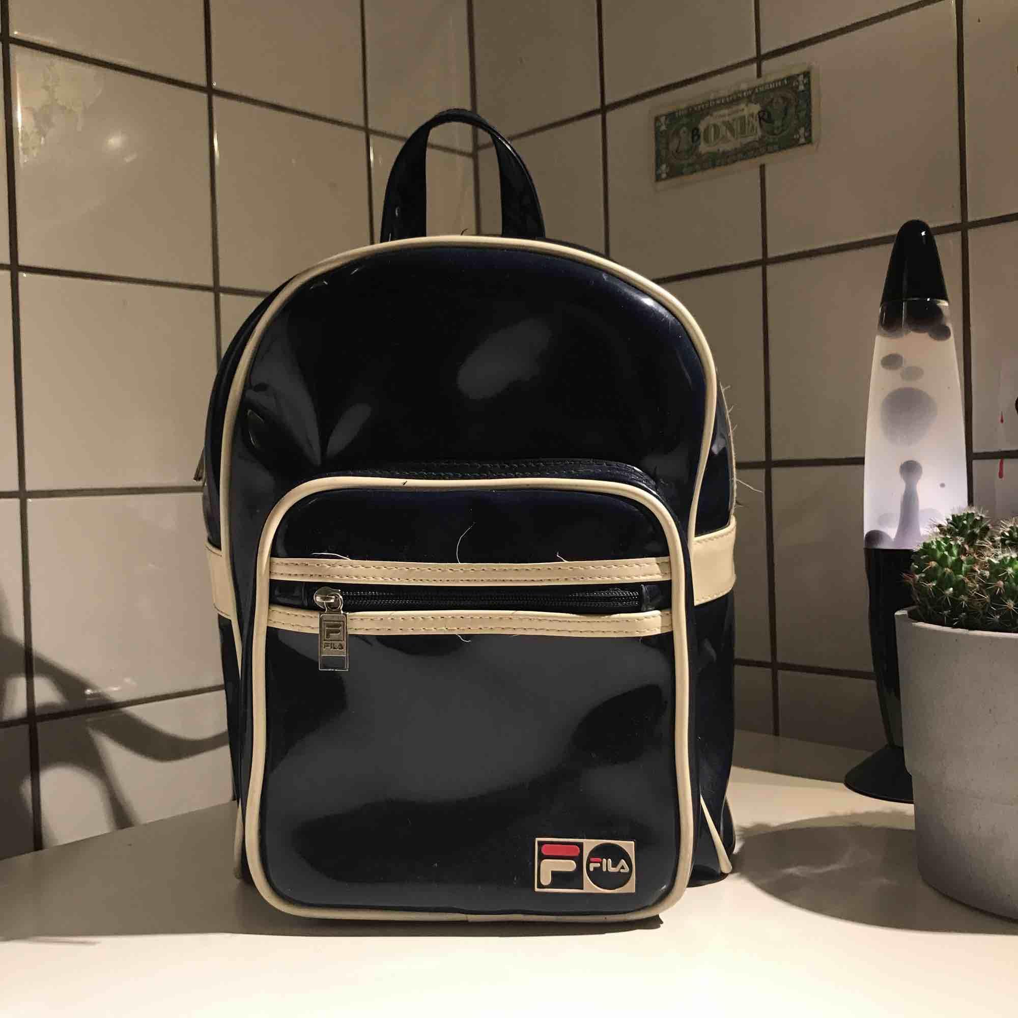 RETRO RYGGSÄCK ❤️ Äkta mörkblå fila ryggsäck i vinyl (plast)! Köpt vintage. Perfekt ryggsäck som får plats med det mesta 🌈 säljer pga inte min stil längre. Obs ❤️frakt ingår inte (50 kr + för frakt)  Mått / 29 cm höjd, 21 cm bred, 12 cm djup . Väskor.