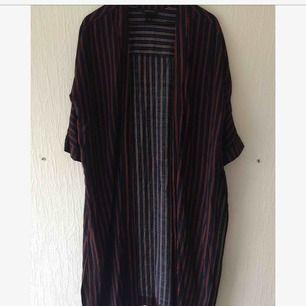 Oanvänd kimono från Monki. Blå/röd-randig med slits på båda sidorna och armbågs-längd på ärmarna. Kan mötas upp i Malmö, annars tillkommer fraktkostnad!