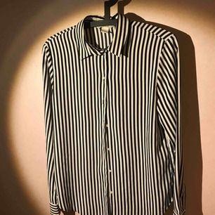 Svartvit randig blus, polyester med silkeskänsla, rak 90-tals modell med smal krage, två knappar i manchetten