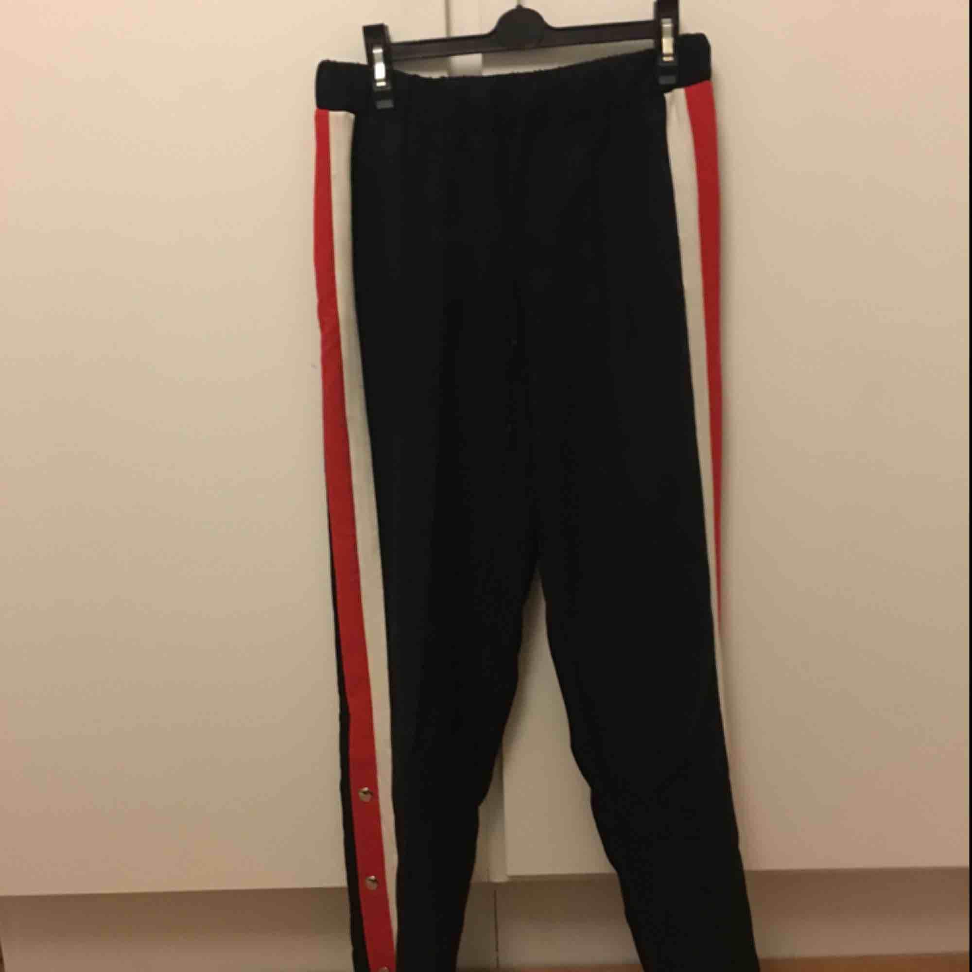 Svarta popperpants med rödvit rand på benen. Knytning i midjan. Frakt på 69kr tillkommer. . Jeans & Byxor.