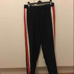 Svarta popperpants med rödvit rand på benen. Knytning i midjan. Frakt på 69kr tillkommer.