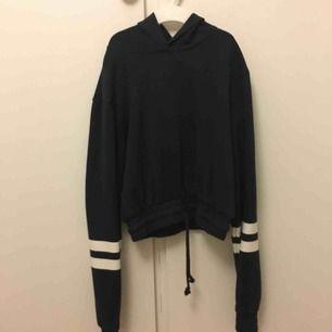 Blå croppad hoodie med knytning i midjan. Frakt på 69kr tillkommer.