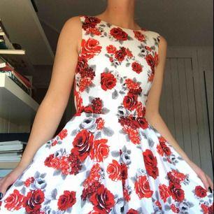 Kort klänning i 50-talsmodell. Bomullssatin med djupt röda rosor på. Båtringning i halsen och klockad kjol. Köparen står för frakt eller möts i Gbg ✨