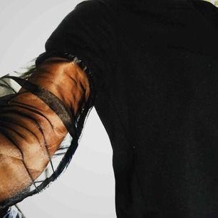 """Svart sweatshirt med """"genomskinliga"""" ärmar. Använd sparsamt. Mjukt tyg inuti."""
