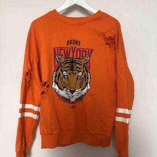 Orange tröja med fina detaljer på ska nu säljas och vill komma till en bättre användning. Säljer på grund av en annan stil:/