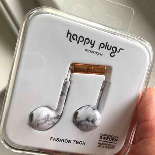 In ears från Happy Plugs. Vit & grå marmor med vit sladd. Passar ej till nyare iPhones, därför är den inte öppnad. Frakt ingår i priset.