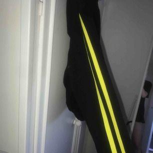 """Hoodie med neon/gula ränder på ärmarna. Lite kortare i modell än en """"vanlig"""" hoodie. Säljes pga används för lite, som ny!"""