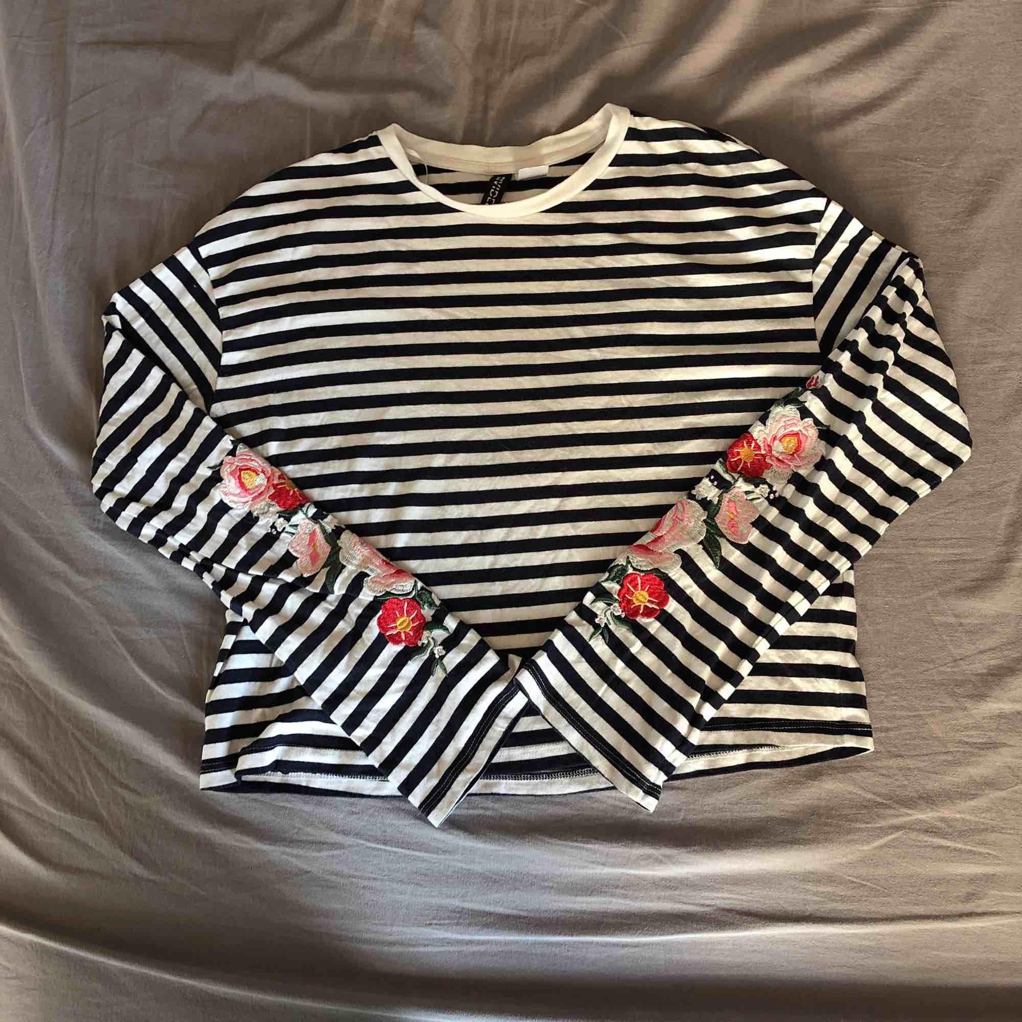 Randig tröja Med blommor på ärmarna från H&M. Säljer för 30kr inklusive frakt. . Toppar.