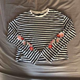 Randig tröja Med blommor på ärmarna från H&M. Säljer för 30kr inklusive frakt.