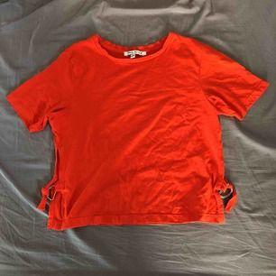 Röd t-shirt med slits på sidorna. Säljer för 20 kr, köparen står för frakt.