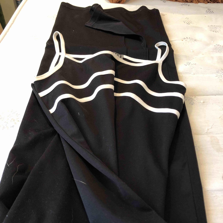En svart maxi Versace klänning men en sportslig känsla. Det står att det är storlek 42 men jag har S eller M och den sitter rätt tajt på mig. . Klänningar.