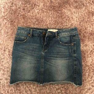 Kort jeanskjol. Mellanblå i färgen. Stl XS.