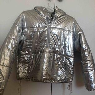 Silverjacka i storlek S dragkedja halvvägs på jackan och dragsko nedtill. Köpt förra året men sparsamt använd Skriv för mer info eller lägg ett bud