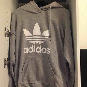 Helt vanlig grå adidas hoodie med luva. Skön passform sitter ej tajt.