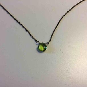 Halsband med grön sten, kedjan har en mörk färg, inte silvrig. Aldrig använt. Köpare betalar för frakt 9kr.