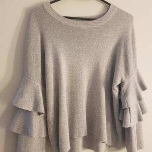 En grå tröja med volang på ärmarna. Använd fåtal gånger. Kommer från bik bok.